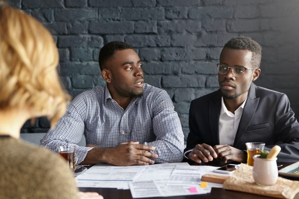 Recruitment and human resources concept. Two doubtful African-American recruiters interviewing unrec